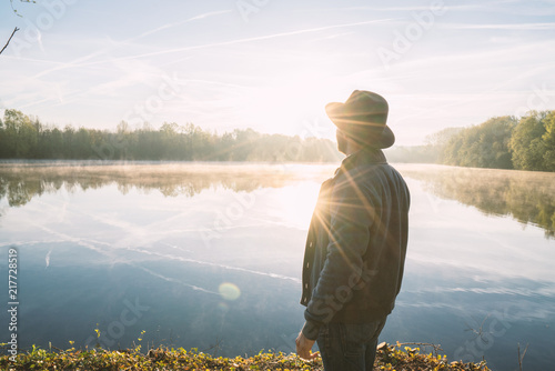 Fotografija  Young man contemplating nature by the lake at sunrise, springtime, France, Europe