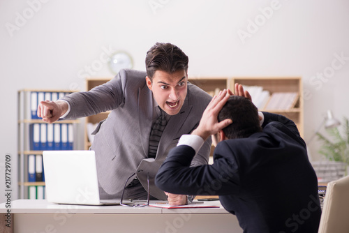 Angry boss shouting at his employee