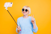 Portrait Of Modern Grandmother Holding And Using Selfie Stick Wi