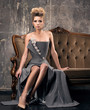 Luxurious woman sitting on a vintage sofa. Formal hair and beautiful grey dress