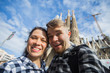 Travel, holidays and people concept - Happy couple taking selfie photo in front of the Sagrada Familia in Barcelona