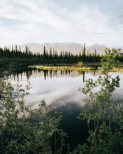 Reflections In Water Near Mountain