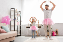 Father And Daughter In Pink Tutu Skirts Dancing Like Ballerinas