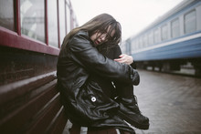 Portrait Of Sad Woman Sitting On Bench At Railroad Station