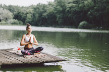 Woman Meditating While Sitting...