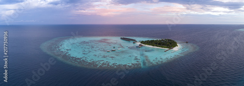 Aerial view of Maldives island against cloudy sky during sunset