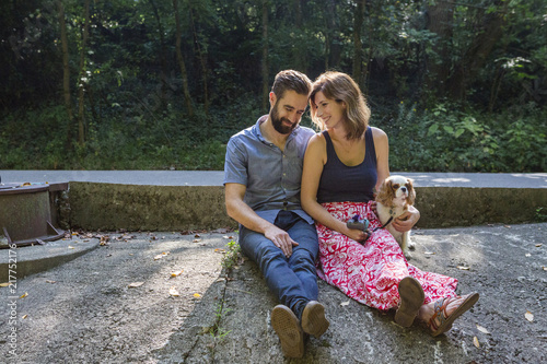 Romantic couple with puppy sitting on rock in forest