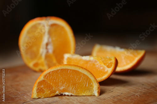 Poster Sap Slices of an orange and its segments lie on the wooden surface of the table.