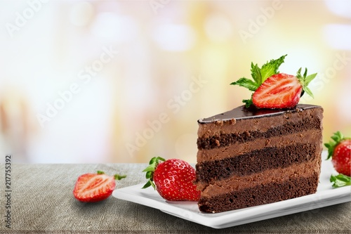 Slice of delicious chocolate cake on desk