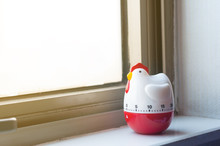 Modern Chicken Timer Next To Windows With Warm Sunrise Lighting, Bell Timer Lay On Room