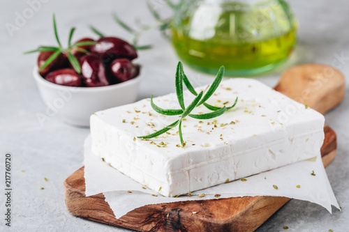 Fototapeta Homemade greek cheese feta with rosemary and herbs on cutting board with olive oil and olives obraz