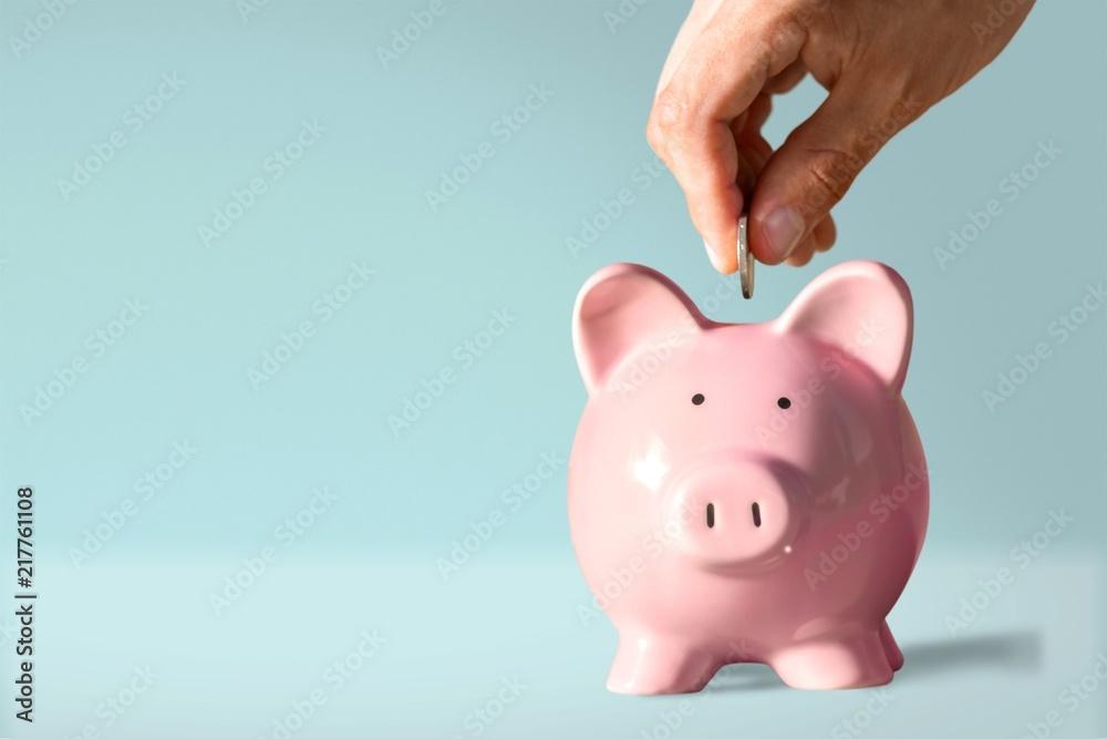 Fototapeta Hand putting coin to piggy bank