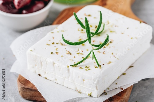 Homemade greek cheese feta with rosemary and herbs on cutting board with olive oil and olives