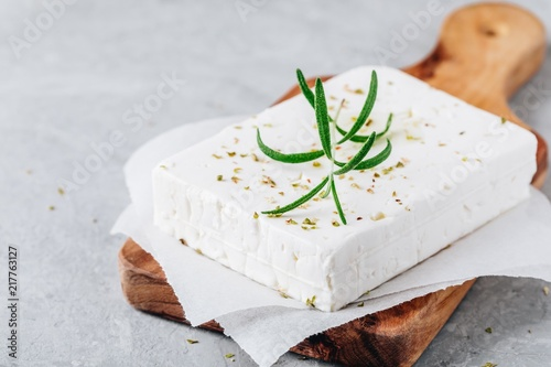 Homemade greek cheese feta with rosemary and herbs on wooden board
