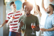 Young excited man with glass of homemade drink pointing at you while dancing with friends at party