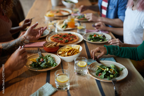 Human hands over plates with food during talk by dinner in modern cafe or restaurant