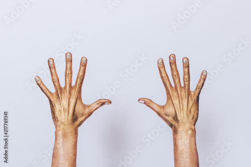 Valokuva  Woman's both hands painted golden sequins showing