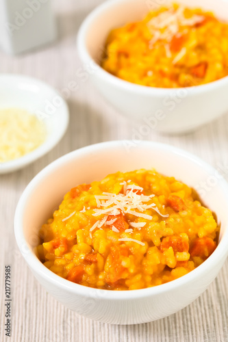 Fresh homemade carrot risotto made with pureed carrot and roasted carrot pieces, grated cheese on top, photographed with natural light (Selective Focus in the middle of first risotto)