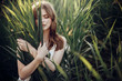Leinwanddruck Bild - beautiful boho girl posing in grass at sunset light near lake. attractive sensual young woman embracing in cane near beach. summer vacation. save environment concept