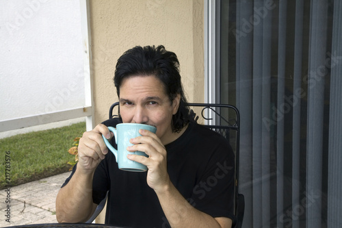 Fotografie, Obraz  Latino man sits and sips from his cup
