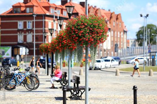Fototapeta Piękne czerwone kwiaty na latarniach ulicznych w centrum miasta Opola. obraz