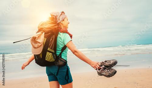 Fotografia  Girl backpacker traveler enjoys with fresh ocean wind