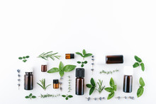 Essential Oils With Botles And Herbs On White Background