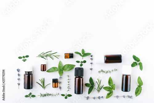 Fotografie, Obraz  essential oils with botles and herbs on white background
