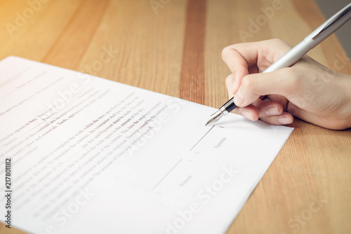 closeup of signing a documentation agreement and pen on the table Wallpaper Mural