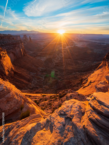 Fototapety, obrazy: Cliff's-edge sandstone Mesa Arch framing an iconic sunrise view of the red rock canyon landscape below.