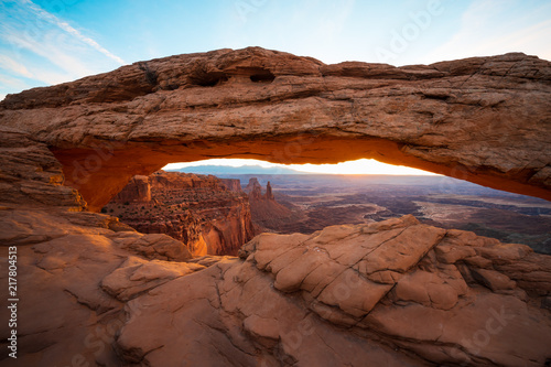 Cliff's-edge sandstone Mesa Arch framing an iconic sunrise view of the red rock canyon landscape below.