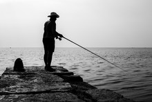 Fisherman Standing On A Pier A...