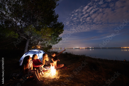 Fotografia  Group of four tourists resting on lake shore at campfire in front of tourist tent under tree, bearded man pointing at bright blue night sky on clear water background
