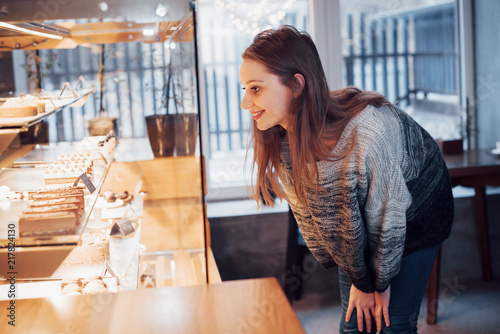 Foto op Plexiglas Bakkerij Happy attractive girl choosing delicious ganaches, praline and chocolates