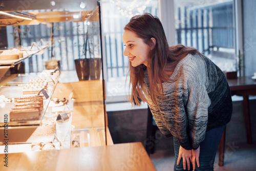 Keuken foto achterwand Bakkerij Happy attractive girl choosing delicious ganaches, praline and chocolates