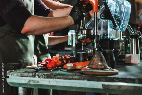 Fotografie, Obraz  man's hand squeezes juice from citrus on a professional mechanical juicer