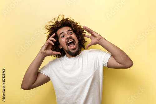 A curly-headed brunet man is shouting and holding his arms near the face Fototapeta