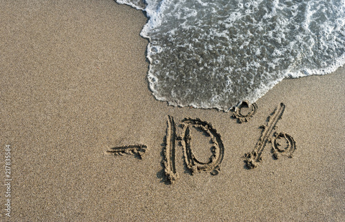Fényképezés  inscription on the sand minus 10 percent, 10 %, sea wave on the sand with the in