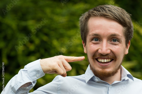 Photo  Young male professional points at his moustache
