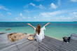 Women wear a sea hat she is happy and sitting on the wood bridge and look to beach seaside, cloud and blue sky is endless background, copy space.
