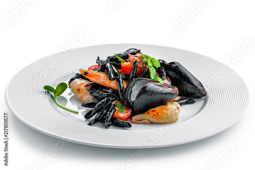 Fototapeta High class healthy Italian seafood pasta meal isolated on white background.. Black squid ink strozzaperti with shrimp and mussels on a plate. obraz