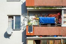 Facade Of A Residential High-rise Building: A Cluttered Balcony With A Homemade Solar Battery, Antennas And A Satellite Dish