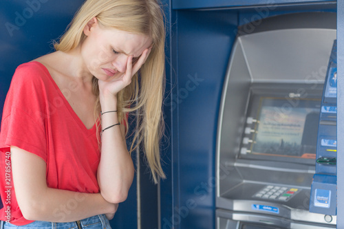 Fotografia, Obraz Sad woman standing in front of a ATM bank machine. No money.