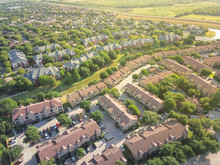 Aerial View Apartment Complex Building And Residential Houses With Canal River Separator. Green And Harmony Architecture Suburb Growing In Irving, Texas, USA. Vast Neighborhood Suburbia At Sunset