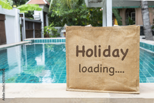 Holiday loading eco bag over blurred swimming pool and ...