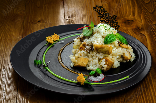 High class healthy Italian rice meal on a wooden table. Excellent creamy risotto cooked in a vegetable broth with porcini mushrooms and parmesan on an exclusive plate.