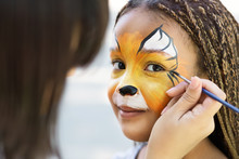 Little Girl Getting Her Face Painted By Face Painting Artist.