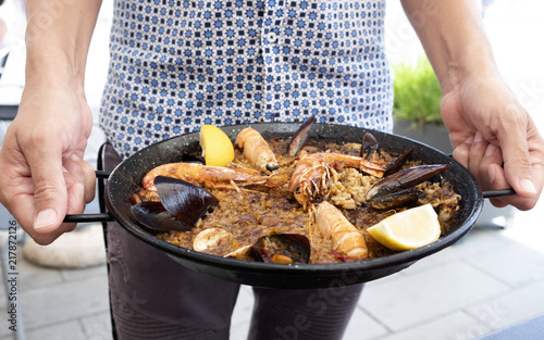 man with a typical spanish seafood paella