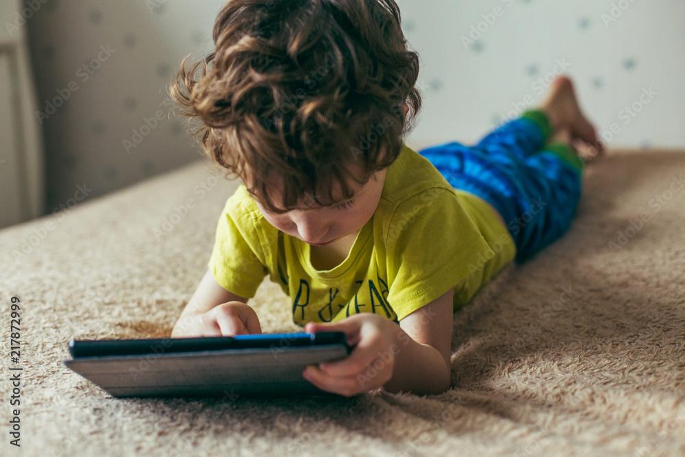 Fototapety, obrazy: Toddler boy staring at tablet. Education, gadget, dependency, technology, addiction, child eyesight, raising children concept