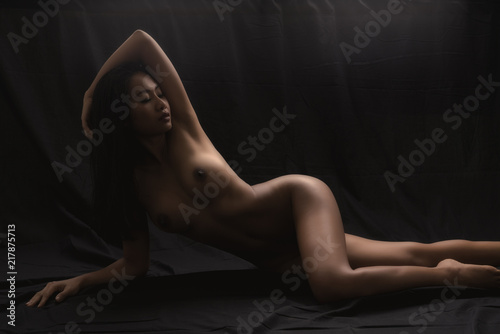 Poster Akt Low key artistic nude of sexy young Asian woman lying down on black cloth background